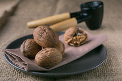 Walnuts on the plate and nutcracker Royalty Free Stock Photography
