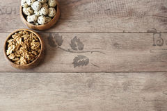 Walnuts and quail eggs in wooden bowls. Rustic wooden background, diffused natural light. Protein nutrients. A different type of concept image for Easter. Copy Stock Photography