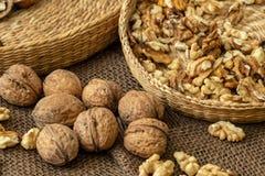 Walnuts on rustic natural burlap, Walnut kernels in wicker basket stock photos