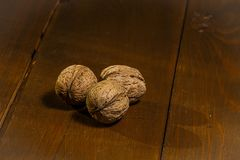 Walnuts on a rustic old wooden table. Three walnuts on a wooden table. Side view. Walnuts on a rustic old wooden table. Three walnuts on a wooden table Stock Photos