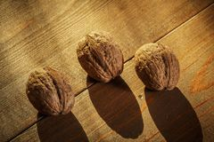 Walnuts on a rustic old wooden table. Three walnuts on a wooden table. Side view. Walnuts on a rustic old wooden table. Three walnuts on a wooden table Royalty Free Stock Images