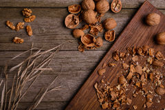 Walnuts on rustic wooden board background with straw copy space for text Stock Photo