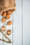 Walnuts in sack and nut cracker on table Royalty Free Stock Image