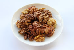 Walnuts on a saucer. On a white background Royalty Free Stock Images