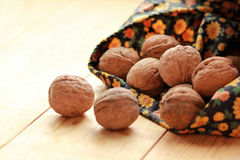 Walnuts scattered from a bag on sunlit light brown wooden floor Royalty Free Stock Images