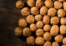 Walnuts scattered on a wooden table stock image