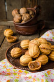 Walnuts shape cookies with condensed milk - dulce de leche in clay bowl on wooden rustic background. Selective focus Royalty Free Stock Image