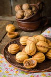 Walnuts shape cookies with condensed milk - dulce de leche in clay bowl on wooden rustic background. Selective focus Stock Photo