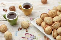 Walnuts Shape Sweet Homemade Cookies with sweet condensed milk filling and nuts on white plate. on old wooden background with cup stock photography