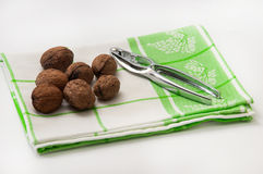 Walnuts in shell with nutcracker on the dish towel Stock Photos