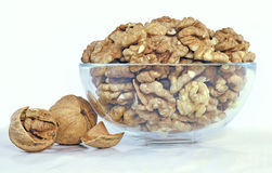 Walnuts in shell or peeled in a glass bowl Royalty Free Stock Images