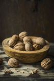 Walnuts with and without shell in a rustic bowl on kitchen table over wooden background. Walnuts with and without shell in rustic bowl on kitchen table over royalty free stock photos