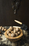 Walnuts with and without shell in a wooden bowl on a wooden rustic background with tongs for cracking nuts Royalty Free Stock Photos