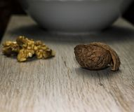Walnuts, shells and bowl. Close up on a wooden surface, dark background Stock Photo