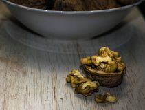 Walnuts, shells and bowl front view. Walnuts, shells and bowl, on a wooden surface, dark background, close up Royalty Free Stock Photos