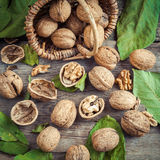 Walnuts and small wicker basket on old wooden table. Royalty Free Stock Photography