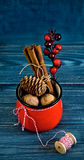 Walnuts, spices and christmas decor in red cup on a blue wood Stock Photo