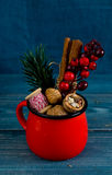Walnuts, spices and christmas decor in red cup on a blue wood Stock Photography
