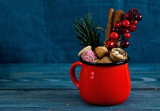 Walnuts, spices and christmas decor in red cup on a blue wood Royalty Free Stock Photos