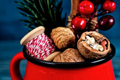 Walnuts, spices and christmas decor in a red cup on a blue wood Stock Images