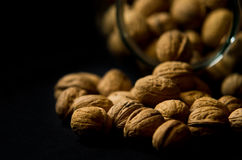 Walnuts Spilling Out of a Glass Jar Royalty Free Stock Photography