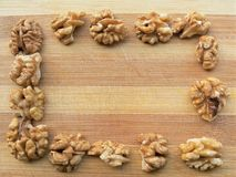 Walnuts square on wooden background Stock Photos