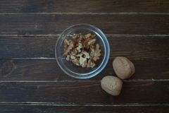 Walnuts in a transparent bowl on wood from above stock photo