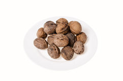 Walnuts on white background and a plate Royalty Free Stock Image