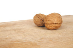 Walnuts on a white background with wooden desk. Walnuts with shell on a white background with wooden desk royalty free stock images