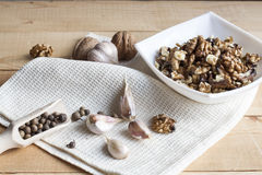 Walnuts in a white bowl, garlic and pepper on a wooden background Royalty Free Stock Photo