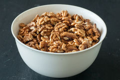 Walnuts in white bowl. On the table Royalty Free Stock Photos