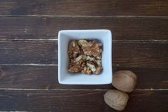 Walnuts in a white bowl on wood from above stock photo