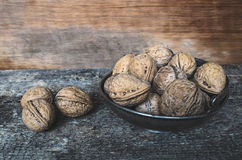 Walnuts. Whole walnuts in a metal bowl on a wooden rustic background Stock Photography