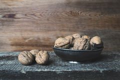Walnuts. Whole walnuts in a metal bowl on a wooden rustic background Royalty Free Stock Images