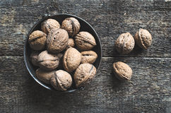 Walnuts. Whole walnuts in a metal bowl on a wooden rustic background, top view Royalty Free Stock Image