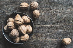 Walnuts. Whole walnuts in a metal bowl on a wooden rustic background, top view Stock Image