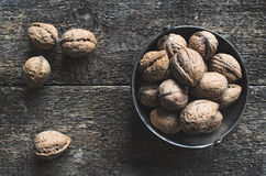 Walnuts. Whole walnuts in a metal bowl on a wooden rustic background, top view Royalty Free Stock Photos