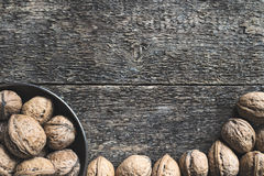 Walnuts. Whole walnuts in a metal bowl on a wooden rustic background, top view Royalty Free Stock Photography
