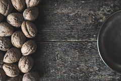 Walnuts. Whole walnuts in a metal bowl on a wooden rustic background, top view Stock Photography