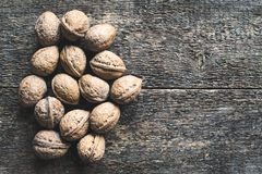 Walnuts. Whole walnuts on a wooden rustic background, top view Royalty Free Stock Images