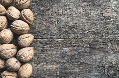 Walnuts. Whole walnuts on a wooden rustic background, top view Royalty Free Stock Photos
