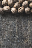 Walnuts. Whole walnuts on a wooden rustic background, top view Stock Images
