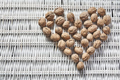 Walnuts on a wicker background. Walnuts in the shape of a heart on a white wicker background Stock Photo