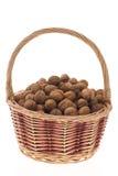 Walnuts in wicker basket. On white background Stock Photos