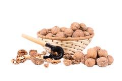 Walnuts on wicker basket and nutcracker. Royalty Free Stock Photos