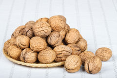 Walnuts. In wicker basket on white tablecloth Stock Images