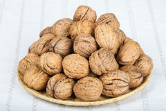 Walnuts. In wicker basket on white tablecloth Stock Photography