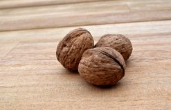 Walnuts on wodden planks. Three Walnuts on wodden planks Royalty Free Stock Photography