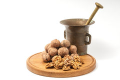 Walnuts on wood plate with mortar. Walnuts and mortar on wood plate with white backround Stock Image