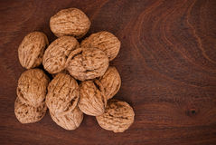 Walnuts on wooden background. Walnuts on rectangular brown wooden background Stock Photos